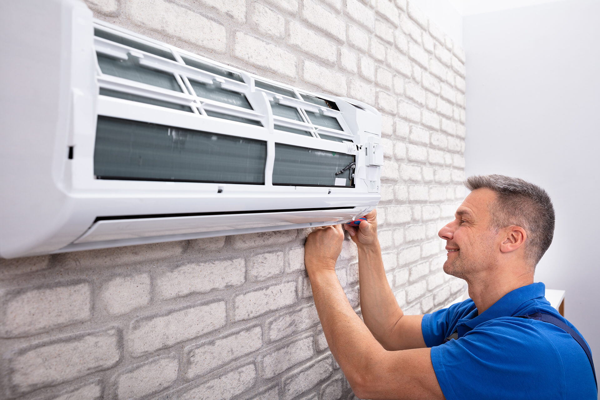 Picture of a man fixing an air conditioner for blog on planning ahead for service